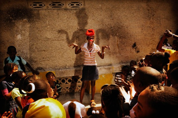 """Port au Prince, Haiti. My-Taelle does a clown routine in front of a group of children. My-Taelle is 10 years old. She lives with her mother, two brothers and four sisters. Her father left the family home. My-Taelle in in fifth grade. Like many other children in Haiti she wasn't able to go to school following the 2010 earthquake. She was happy to be back at school when a temporary classroom was set up because this seemed like normality was returning to her life. """"I dream of becoming a clown. I'll be able to make other children happy. Many people were sad after the earthquake because they lost family members or their houses. I'm glad that I can make people laugh."""""""