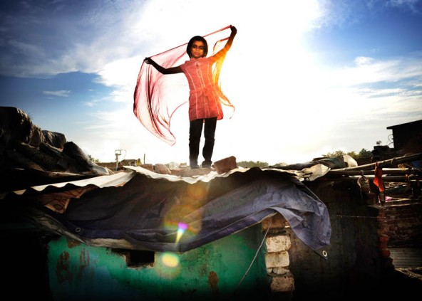 """New Delhi, India. Sabina stands on the roof of one of the shacks in the slum where she lives holding up a brightly coloured scarf. Sabina is 9 years old and lives with her parents and brother in a slum in Delhi. Her father is a rickshaw driver and the family has very little money. The slum where they live is dirty and smelly since there are thousands of people living in a very confined space. """"I am always wearing the second hand clothes of my nieces. Everything is dirty and dingy. I dream of beautiful dresses which would make me look like a movie star and I would be able to shine and dance through the slum. Everyone would think that I'm the most beautiful girl in Delhi."""""""