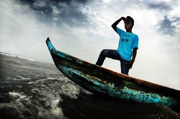 """Monrovia, Liberia. Varney Parkir is 14 years old. Here he stands at the front of a boat. Parkir was born in Liberia and his mother died when he was a baby. His father couldn't provide for the family and his village doesn't have a school so he went to Monrovia, the capital, to go and live with his uncle. His father, stepmother and sister stayed behind in their village. Varney never goes to visit them. The people in the village were jealous of him so he doesn't feel welcome back home anymore. """"I dream of becoming a captain of a big ship. With the ship I want to travel to Robertsport in Grand Cape Mount County. That's where I was born."""""""