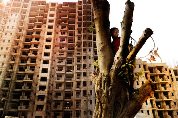 Aniket sitting in a tree. 10 year old Aniket lives with his parents and sister in a slum in New Delhi. He wants to become an architect. Behind the house where he lives a large multi-story building is being built. Aniket would like to live there one day.