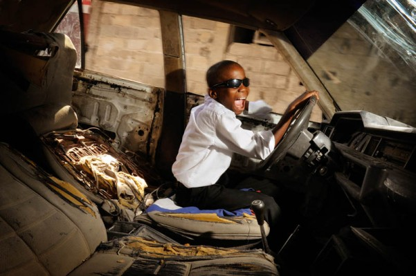 """Port au Prince, Haiti. Blaise pretends to drive an old, broken car. Blaise Bedzermitki Leveltson is 12 years old. He has seven brothers and one sister. His father is a soldier. He was deeply traumatised by the 2010 earthquake but he is an active and happy boy. Blaise has many dreams. He'd like to become a driver or a mechanic but he also admires Michael Jackson and Ronaldo. """"Well, I dream about so many things. If I really had to choose I would struggle. If I'm being sensible I should be a driver, but I also dream about being like Michael Jackson. It's really hard to choose."""""""