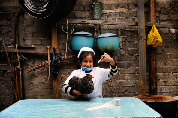 """Djarida, dressed up as a veterinarian, holds a chicken and pretends to inject it with a syringe. Djarida is 8 years old and lives in San Cristobal de las Casas in Chiapas, Mexico. She is from a Mayan family background. Mayans are one of the indigenous peoples of Mexico, many of whom today are poor and disadvantaged. Djarida's father left the family home and her mother works as a housekeeper in the city. Djarida loves all animals, especially dogs. """"Many girls are not allowed to go to school or only for a short time. Then they are required to help at home, to get married or to work. I'm happy going to school every day. When I grow up I want to be a veterinarian. I have to study hard but I'm sure I will succeed."""""""